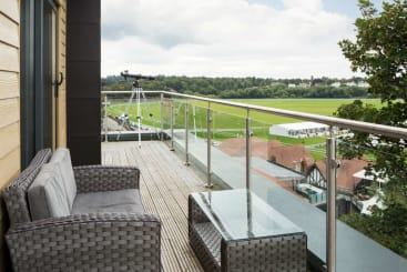 The balcony of the ascot suite at Roomzzz Chester with telescope looking out over the racecourse.