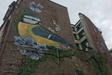 Street art of a blue tot on the side of a building in Manchester's Northern Quarter