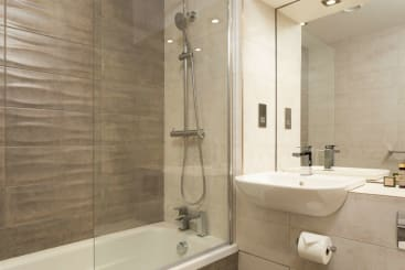 An ensuite bathroom with a bath in a Liberty Suite at Roomzzz London Stratford