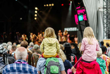 A family watching a band at a festival