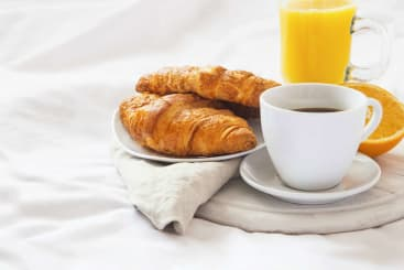 Croissants in bed with fresh orange juice and coffee