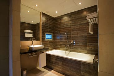 The bathroom with TV in the emperor suite in Manchester Roomzzz