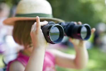 Young girl looking through binoculars at horse races
