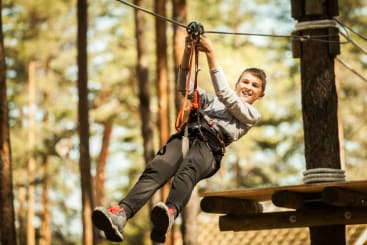 boy ziplining through the woods