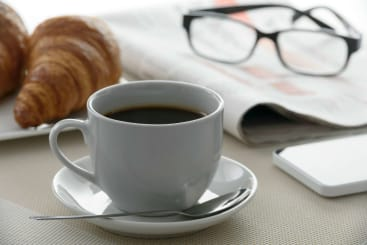 A cup of coffee on a table next to a croissant, newspaper and glasses