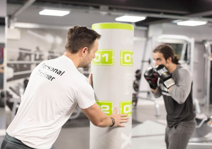 A student working with an IconInc personal trainer in the on-site gym.