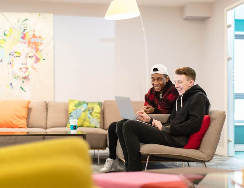 Students in the communal lounge browsing on a laptop together